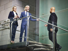 Senior Corporate Executive Welcoming Visitor On Stair Of Modern Office Building