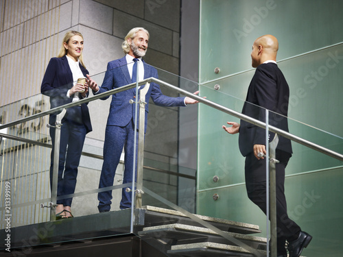 Obraz na płótnie senior corporate executive welcoming visitor on stair of modern office building