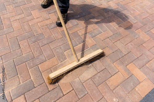 Brushing kiln dried sand into newly laid block paving driveway Fotobehang