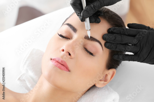 Valokuva Young woman undergoing procedure of eyebrow permanent makeup in beauty salon