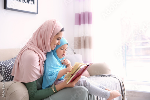 Muslim woman reading Quran to her daughter at home