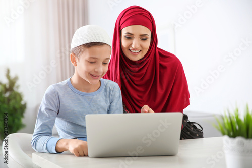Muslim woman using laptop with her son at home