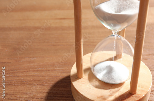 Fotografiet  Hourglass with flowing sand on wooden background. Time management