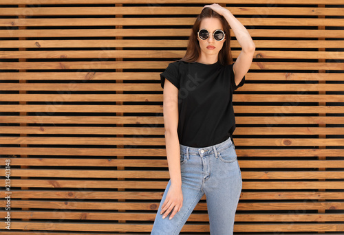 Fotografía Young woman wearing black t-shirt against wooden wall on street