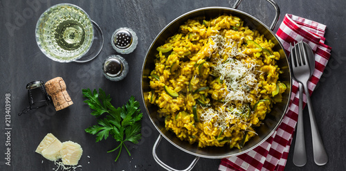 Photo  banner of Italian dish yellow Risotto milanese with saffron, zucchini and Parmesan cheese on a black slate table with white wine in a glass
