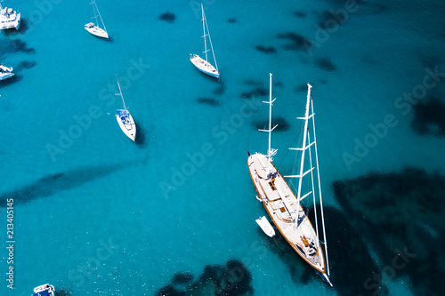 Photo  Aerial view of some yachts and a big sailboat on an emerald and transparent Mediterranean sea