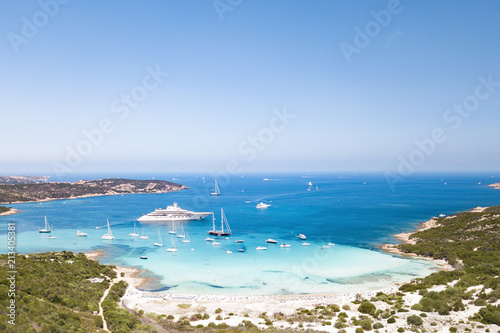 Photo  Aerial view of an emerald and transparent mediterranean sea with a white beach and some yachts