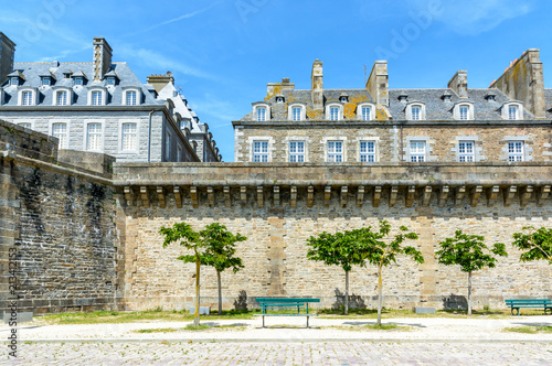 Photo  View of the surrounding wall of the city of Saint-Malo in Brittany, France, a small park with trees and benches at the foot of the wall and granite residential buildings protruding above the rampart