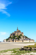 General View Of The Mont Saint-Michel Tidal Island, Located In France On The Limit Between Normandy And Brittany, From The Bay At Low Tide Under A Summer Blue Sky.