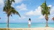 Young beautiful woman on tropical seashore. Happy girl relaxing at white sand tropical beach