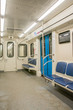 View of bright empty interior of modern subway train car. Contemporary inside space of the underground railway carriage with no one inside, empty seats.