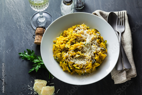 Italian dish yellow Risotto milanese with saffron, zucchini and Parmesan cheese on a black slate table with white wine in a glass Canvas Print