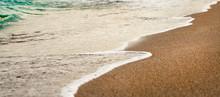 Waves Wash Over Golden Sand On Beach