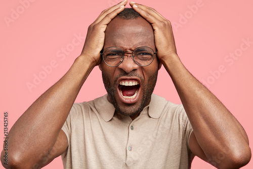 Fotografía  Close up portrait of desperate African American male regrets something wrong, frowns face in discontent, opens mouth widely, dressed in t shirt, isolated over pink background