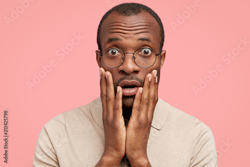 Photo of scared handsome dark skinned young male hears sudden negative news, keeps palms on cheeks, wears spectacles and casual clothing, expresses great disbelief, isolated over pink background