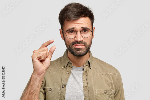 That`s all I have! Displeased bearded young male model shapes something tiny with hand, makes small gesture, discontet with salary, stands alone against white studio wall. Man talks about size