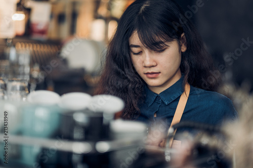 Fotografía  asian woman barista making hot coffee with machine at counter bar in cafe restaurant,Food and drink service concept