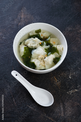 White bowl of chinese wonton soup over dark brown stone background, vertical shot, selective focus