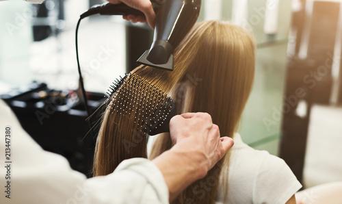 Obraz na plátně Making hairstyle using hair dryer