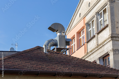 Fotomural Ventilation chimney on the roof with gutter near old apartment house