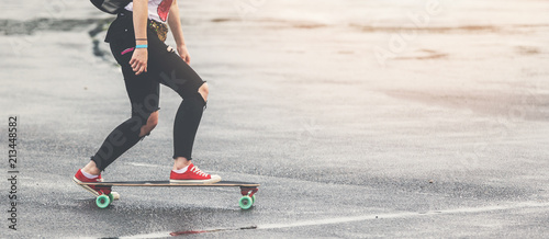 girl with ripped jeans and red sneakers riding longbord on the street