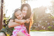 Young mother and daughter hugging in sunlight in beautiful nature. Concept of happy loving family
