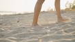 Legs of a girl walking along a sandy beach at sunset. Slow motion.