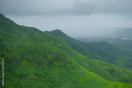 Poster Donkergrijs Green landscape surrounded by hills, mountains in monsoon season