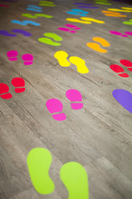 Shot Of Many Colorful Footsteps On A Wooden Floor That Are Crowding Together