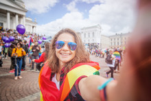 A Beautiful Young Happy Woman With A Rainbow Flag, A Symbol Of The LGBT Community, Makes A Selfie On A Mobile Phone On A Pride In A European City. Human Rights, Equality, LGBT, Freedom And Happiness