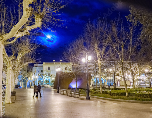 Logrono, La Rioja, Spain. April 23, 2018: Nighttime image of a central plaza of logrono with the full moon partially covered by clouds, very illuminated by streetlights and people walking