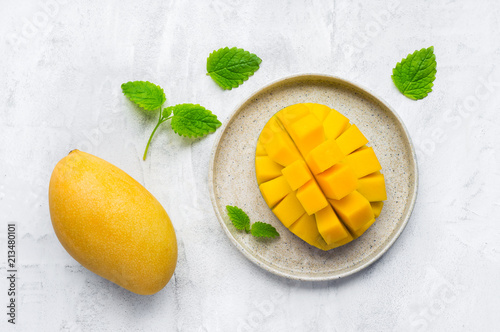 Healthy breakfast. Sliced yellow thai mango fruit on plate. Top view. Concrete background.
