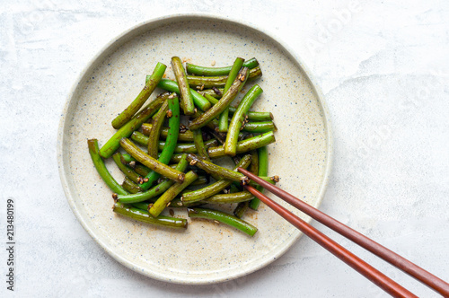 Eating grilled garlic scapes salad. Traditional Korean Chive Salad (Buchu Muchim). Top view.