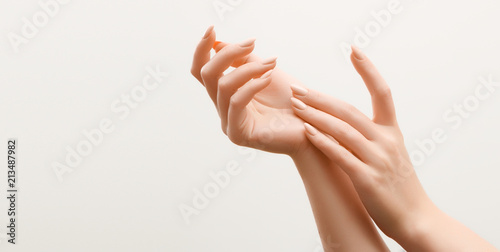 Poster Manicure Beautiful Woman Hands. Female Hands Applying Cream, Lotion. Spa and Manicure concept. Female hands with french manicure. Soft skin, skincare concept. Hand Skin Care.
