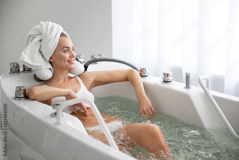 Fototapeta Portrait of beaming female relaxing during treatment procedure in water. She looking at window