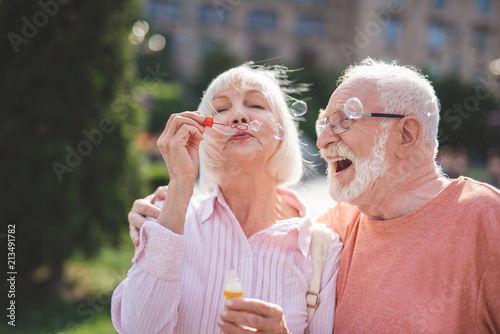 Cheerful lady holding bottle with soap water and blowing bubbles on street. Exited mature male is hugging and looking at her with content. They are embracing each other with pleasure