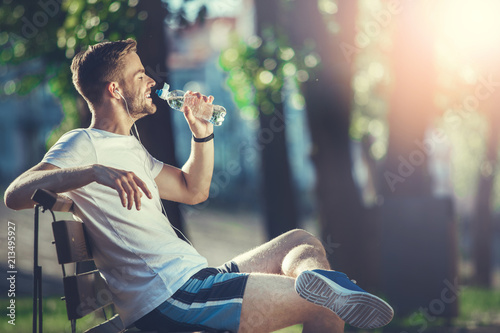 In de dag Ontspanning Full length profile of smiling man sitting on bench and drinking water. He is satisfied with morning workout
