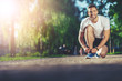 Leinwanddruck Bild - Full length portrait of smiling athlete kneeling and fixing shoelaces outdoors. He is joyfully looking at camera while listening to music with earphones. Copy space in left side