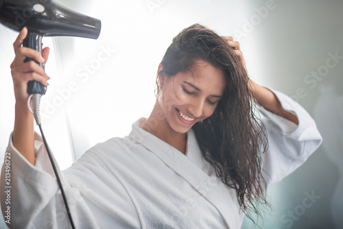 Portrait of cheerful female blowing wind on hair after taking shower. She gesticulating hands and having fun