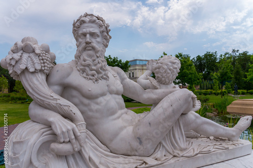 a statue of the god Zeus sitting with an angel and holding a cornucopia Wallpaper Mural