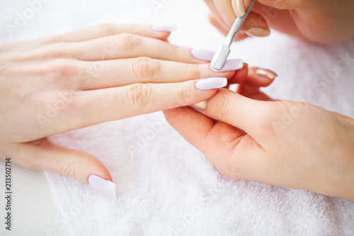 Deurstickers Manicure SPA manicure. Woman in a nail salon receiving a manicure by a beautician