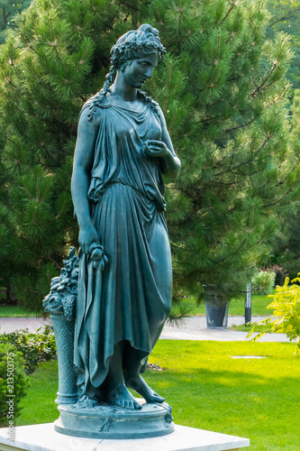 Bronze statue of a woman with a basket of flowers in the park on the background Canvas-taulu
