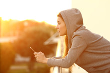 Teen Holding A Smart Phone Looking Away At Sunset