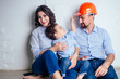 Leinwandbild Motiv happy family handsome man in helmet hardhat and charming woman and their cute little son sitting on the floor against a white wall . concept of buying repairs house ( apartment ) by young family