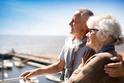 Leinwand Poster Affectionate mature couple enjoying summer vacation by seaside at resort
