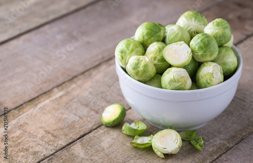 Raw brussels sprouts in white bowl on wooden rustic desk.