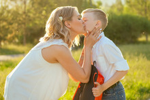 Mother Kissing Son Before Going To School . Stylish And Young Schoolboy In A White Shirt And Jeans With A Backpack In The Park