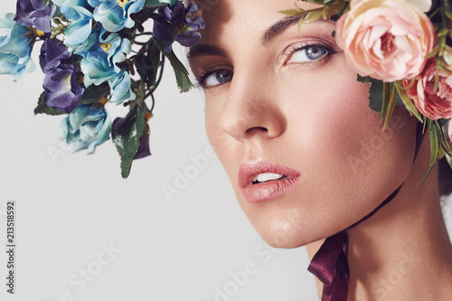 Montage in der Fensternische Spa A portrait of a young beautiful woman with flowers on the head. Spring fashion photo. Skin care concept, beauty spa, bio product.