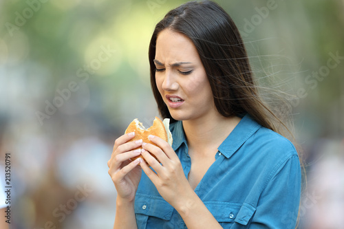 Woman eating a burger with bad taste Fototapete