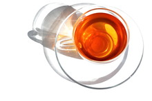 Glass Transparent Cup Of Warm Tea And Dish In Morning Bright Rays Sunlight With Shadow On White Background. Isolated. Top View